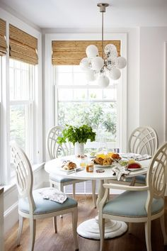 Elegant corner breakfast nook features white glass cluster pendant over round white dining table surrounded by white trellis dining chairs accented with baby blue seat cushions situated in front of windows dressed in bamboo roman shades.