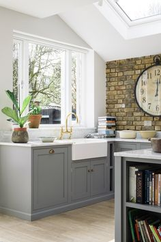 Sunshine streams in though this lovely big window in this beautiful South London kitchen. Lead grey cupboards are complimented by deVOL Aged Brass 'Ionian' taps and a classic Villeroy & Boch Farmhouse sink.