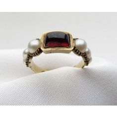 """Circa 1820. This is an exquisite Georgian mourning ring, centered by a beautiful cabochon cut garnet and accented by six pearls. The mounting is 18KT yellow gold. The interior is engraved """"Elizabeth Bloxam died 5 Dec 1826 aged 58""""."""