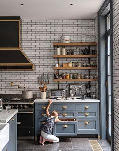Ceiling-high subway tiles with contrasting gray grout are a dramatic backdrop for gray cabinetry warmed up by wooden open shelving and brass hardware.