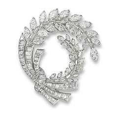 A DIAMOND BROOCH, BY CARTIER Of openwork circular design, the stylised bow set with baguette-cut diamonds and a brilliant-cut diamond tie to twin cascading branches of marquise-cut diamonds, circa 1960, 5.5 cm long, in red leather Cartier case Signed Cartier, No. K9921