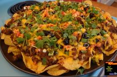 Nachos are a crowd-pleasing appetizer.  This recipe goes beyond cheese and jalapenos.  Crispy tortilla chips are piled high with ground beef, chopped tomatoes, sour cream, olives and much more.