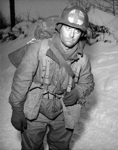 An exhausted American medic returning from the front  during the Battle of the Bulge.