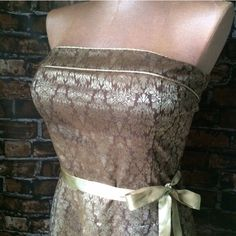 """Brown & gold brocade dress Teeze Me strapless brown & gold brocade fit n' flare dress with gold satin waist sash. Back zipper. Size is 13. Bust measures 17"""" across flat. 19"""" following the curve of the bust. 17"""" across the waist. The length is 36"""" (22.5"""" from dropped waist hem to bottom hem). Mannequin bust is 39"""" for fit comparison. 100% polyester. Not interested in trades. Teeze Me Dresses Strapless"""
