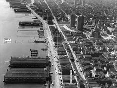 Aerial photograph looking south along Delaware Avenue shows demolition of Chestnut Street Pier in preparation for the Penn's Landing redevelopment project. Society Hill Towers and cleared blocks around Dock Street shown, as is Market-Frankford Line portal and tracks north of Market Street. October 20th 1965