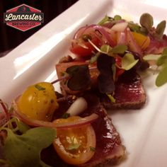 Tuna Carpaccio Appetizer: heirloom tomato, greens, capers, olives, red onion, balsamic glaze.