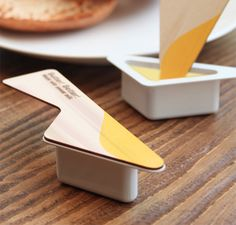 """Butter! Better! designed by Yeongkeun  """"Whenever we eat bread, at the picnic, in the cafe or airplane, we usually use disposable butter. I replaced its ordinary container lid with a wooden, knife shaped one. This way butter can be easily and quickly spread. Butter has 4 flavors which allow the user to make a choice, just as he would chose his favorite ice-cream. This container is not only easy and fast to use but also it makes daily routine of spreading butter more fun and exciting."""""""