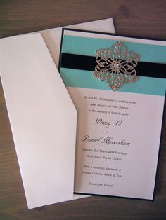 This wedding invitation called Metal Moonstone has been made using pearlescent black card (285gsm), pearlescent turquoise paper, black satin ribbon and a unique metal flower with a rhinestone in the middle. It comes with a matching pearlescent white envelope. (https://www.etsy.com/listing/119845245/metal-moonstone-wedding-invitation)