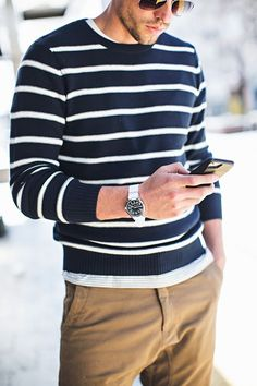 Great men's outfit for warm weather: striped sweater, khaki joggers, silver watch, aviator sunglasses. .