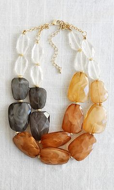 Bring a natural and classy touch to your favorite basic shift dress. This necklace featuring acrylic 'stones' in earthy shades contrasted by gold hardware is unforgettably chic.