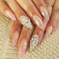 Punta almendra con difuminado en rosa, dorado y natural en cama de la uña y dedo acento con diferentes tamaños de piedras