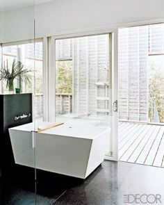 This indoor-outdoor bathroom incorporates black slate floor tiles and a sliding door that leads to a cedar-slatted shower on the terrace.