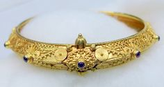 """VINTAGE 22 KARAT SOLID GOLD HINGE BRACELET BANGLE FROM RAJASTHAN INDIA. BEAUTIFUL DETAILED DESIGN ,TRIANGULAR SHAPE AND SATED RUBY COLOR STONES, SECURE SCREW CLOSING (SCREW DO NOT COME FULL OUT, IT IS LOCKED IN END).FULL HANDCRAFTED GREAT PIECE FOR YOUR JEWELRY COLLECTION. BUYER WILL GET GOLD TEST REPORT FOR THIS ITEM FOR FREE. TOTAL WEIGHT -31 GRAMS(1.08 OUNCE), INNER DIAMETER- 6.1 CM(2.37"""") AVAILABLE SAME IN DIFFERENT SIZES TOO, WIDTH-1.2 CM, MATERIAL -SOLID 22 KARAT GOLD."""