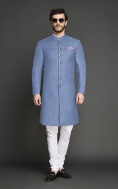 This Airy Blue Achkan is a refined alternative to traditional ceremonial colors. Tailored & designed for an ambitious modern man, this Achkan features interesting tailoring details over bling and will make you look every bit elegant and sophisticated. Sherwani For Men Wedding, Wedding Dresses Men Indian, Wedding Dress Men, Wedding Suits, Indian Men Fashion, Indian Bridal Fashion, Mens Fashion Wear, Kurta Men, Mens Sherwani