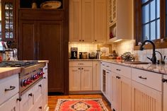 A smaller country kitchen with light granite countertops in beige and a combination of aged white cabinets with striped details and rich, dark wood cabinetry with long iron handles. Accents in this kitchen include an antler dish, framed botanicals, and a bear-and-honeypot cookie jar.