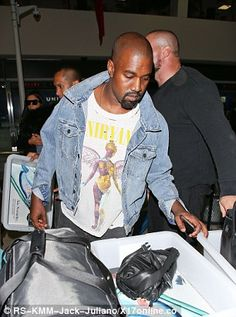 Rock star: The rapper showed off his Nirvana t-shirt underneath his jacket