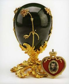 Faberge Eggs: Imperial Pansy Egg 1899. The polished and carved jade  (154 diamonds totaling 1.54 carats, 170 rubies totaling 6.46 carats, and 4 citrines, total weight .60 carat). Features a silver gilt base of spiraling and twisting leaves and twigs which supports the egg and opens to reveal a magnificent heart shaped red agate picture frame with a diamond set rim (.29 ct), and one diamond in the crown (.04 ct).