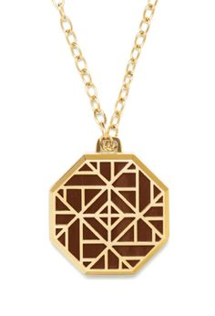 A statement piece, the Tory Burch fretwork pendant swivels open to reveal a solid perfume.