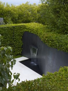 Pacific Heights Residence by Lutsko Associates, San Francisco, California | I generally despise hedges but this works — not only for privacy but as a brilliant contrast to the white patio and the black steel. Love both the hedge contained by steel framework and the subtlety of the waterfall.