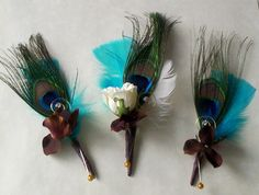 Peacock boutonnieres with a little flair. I hate the bright turquoise feathers behind the peacock feathers. but I like the little white rose & other small flowers in front.