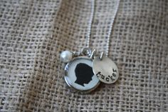 Hand Stamped Sterling Silver Disc with a Silhouette Charm with a Pearl on a Chain. $35.00, via Etsy.