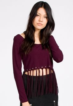 Be a grunge goddess in Shown To Scale's Shake It Top. Long sleeve crop top features tassels tied into silver eyelets. Goes perfect with the Nightrider Skirt.  $50