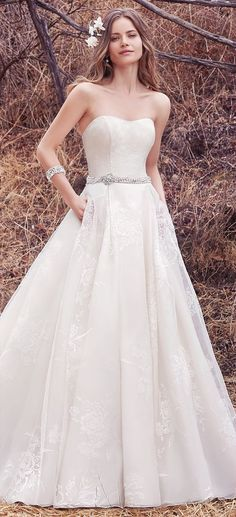 This sweet and elegant ballgown features layers of Vega Organza. A strapless scoop neckline and sheer pockets complete the ethereal romance of this wedding dress. Finished with pearl buttons over zipper and inner elastic closure. Pearl and Swarovski crystal belt featuring beaded brooch sold separately.