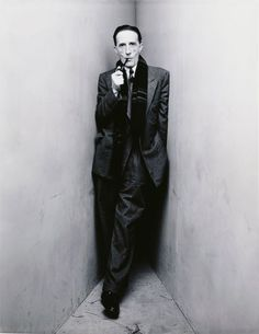 Duchamp sports a suit and scarf keenly.