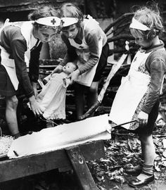 Children pretend to be nurses in the ruins of a bombed London, WWII