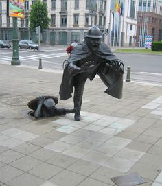 Sculpture by Tom Frantzen in Brussels, Belgium. The piece was completed in 1985 outside the Communauté Française building and depicts a young man emerging from the sewer to grab the leg of a police officer. Stonehenge, Bruges, Budapest, Visit Belgium, Street Installation, Colossal Art, Voyage Europe, Land Art, Public Art