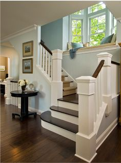 Dark floors with lots of white trim work and staircase