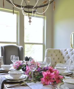 beautiful dining room with white ceramic and pewter dinnerware and bright flowers in centerpiece by arte italica_
