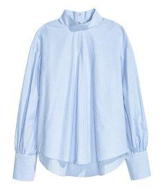 Weiß. Langarmbluse aus luftigem Webstoff. Die Bluse hat einen Stehkragen, überschnittene Schultern und weite Ärmel mit breiter, enger Manschette. Verdeckte