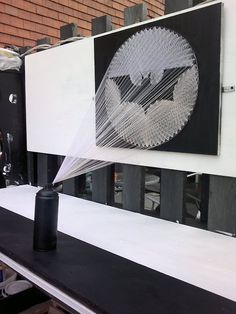 3D thread work of artist Perspicere's latest creation on Batman, A sculptural installation depicts a black spray can shooting out the widely recognized bat signal that is typically a strong beam of light shot into the night sky as a distress signal, calling for the aid of the nocturnal superhero.