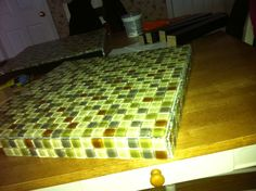 Ikea Lack side tables X2 (7 bucks)  Recycled Glass tiles X4 (20 bucks)  Grout, Seal (10 bucks)    Recycled glass tiling of Ikea (Lack) side tables.