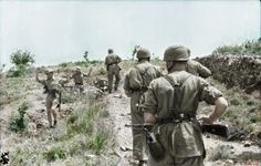 Surrendering commonwealth soldiers been taken POW by German Fallschirmjäger, Crete, 1941. Colorization and description by Mike Gepp.