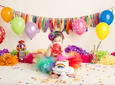 Baby girl in rainbow themed baby cake smash photo by Brandie Narola Photography