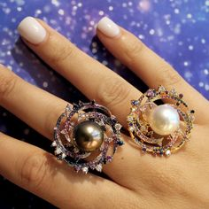 Autore Stardust Spiral Galaxy pearl rings, with a white Australian South Sea pearl and a black blue purple Tahitian pearl, surrounded by a star storm of galaxy gemstones. Out of this world modern design. The best fashion forward design jewellery moments from Baselworld 2017 on day 3: http://www.thejewelleryeditor.com/jewellery/top-5/baselworld-jewellery-day-three-highlights/ #jewelry