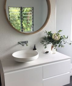 Feature wall of Penny Round tiles, Omvivo Vanity Basin and Caesarstone Calacatta Nuvo bench top.