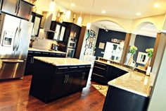 Kitchen with arches to keep the floor plan open concept, yet delineate spaces.  Also, dark cabinets with silver hardware/appliances and light granite countertops.