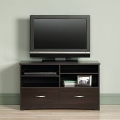 """Add the Sauder Beginnings Cinnamon Cherry 42"""" TV Stand to your living room or bedroom for the new perfect spot to place your TV. Cinnamon cherry brown finish. 2 drawers with silver pulls. 4 shelves, includes 2 adjustable. Holds TVs up to 46"""" and 95 pounds. Contemporary minimalist style. Sauder Beginnings Cinnamon Cherry 42"""" 