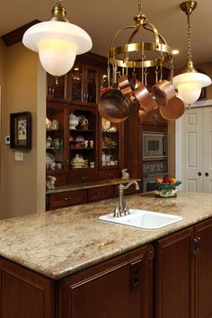 Kitchen Remodel, Daniels Design and Remodeling, dark cabinets, glass cabinets, island, countertops, open space, luxurious, tile floors, contemporary, granite countertops, hanging lights, light colored walls