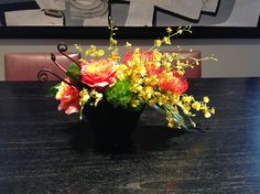 Low arrangement with pin cushion protea, free spirit rose, fiddle headed fern, green trick & oncidium orchids.