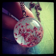 """Handmade red flower necklace. This necklace has a real dried red flower carefully embedded into a resin sphere.  Pendant size: orb is 25 mm (1"""") in diameter. 20"""" copper chain."""