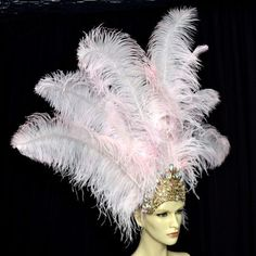 Feather headpiece height is 20 (51cm) plus 4 crown width. (dimension is taken at the center of the headdress where the tallest feather is located)  Feather Color: Light Pink Ostrich Feathers  The exclusive lite weight Gold crown design is created with AB Crystal Stones over Acrylic base    This Feather Headdress is made with premium, first quality hand selected Ostrich Plumes wing feathers. Feathers cover the front and sides of the headdress, the back is open.  Wing feathers are the most…