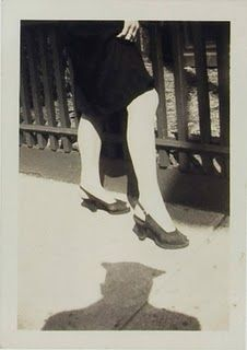 A woman's legs and heels / the photographer's shadow. Found snapshot, mid-century.