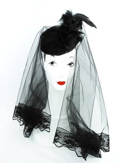This hat is a black funeral hat with black feathers ,black silk rose and black veiling can be worn with the veil over the hat or behind ( see images). It is a pillbox style and attaches with hat elast