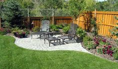 wooden privacy fence + corner seating area + landscaping  Rock Bottom Landscaping
