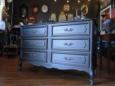 This is a dark, cold, silver color, smooth and sleek with a pewter color detail and pulls. Drawer interiors are a pale aqua. Modern Vintage