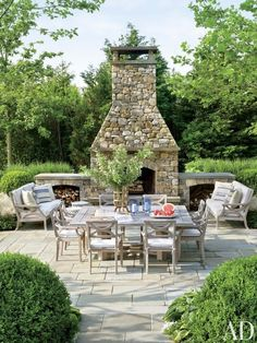 Arranged near the outdoor fireplace of a Southampton home by Carrier and Company Interiors and architect John David Rose are Country Casual sofas and chairs cushioned in a Sunbrella fabric. | archdigest.com